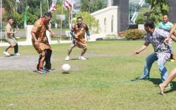 Kapolres Palangka Raya AKBP Lili Warli ketika menggiring bola sambil dibayang-bayangi lawannya.