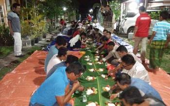 Ratusan warga saat menyantap nasi lewet yang dibuat dengan panjang 100 meter.