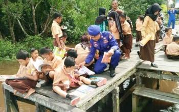 Sejumlah anak sekolah di tepi Sungai Mentaya asyik membaca di lanting dengan didampingi guru dan anggota Ditpolairud.