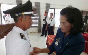 Camat Sepang Rosalia memasang tanda jabatan pejabat kepala desa
