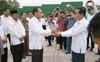 Bupati Arton S Dohong (kiri) menyerahkan bantuan untuk Ketua Dewan Pengurus Daerah Dewan Masjid Indonesia Kabupaten Gunung Mas M Rusdi, Rabu (30/8/2017)