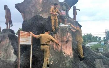 Wabup Kobar Ahmadi Riansyah bersama ajudannya melepas baju yang dipasang oleh orang yang tak bertanggung jawab pada patung Orangutan di Bundaran Orangutan Kecamatan Kumai, Senin (4/9/2017).
