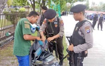 Anggota Polda Kalteng memeriksa tas bawaan wartawan saat masuk ke Polda Kalteng