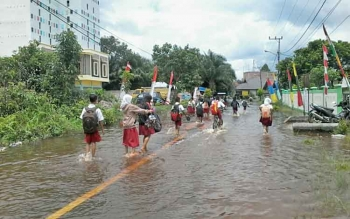 Puluhan murid SDN3 Kelurahan Kasongan Lama terpaksa harus basah kuyup saat pulang sekolah di jalan yang kebanjiran, Selasa (5/9/2017).