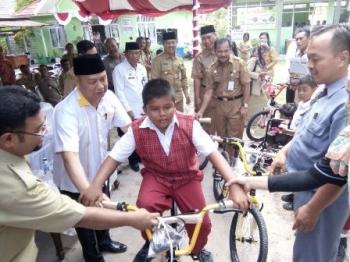 Ketua Komisi C DPRD Kota Palangka Raya Rusliansyah (dua kiri) menyerahkan bantuan sepeda secara simbolis kepada anak penyandang disabilitas di Kelurahan Sabaru, Selasa (5/9/2017).