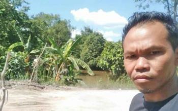 Ahmad, warga Desa Telangkah mengecek kondisi Jalan Trans Kalimantan antara Kasongan-Kereng Pangi yang ambles guna memperkirakan agar mobilnya bisa lancar lewat jalan rusak ini, Kamis (7/9/2017)