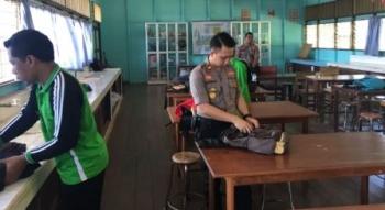 Kapolsek Parenggean Iptu Triono Raharja saat melakukan pemeriksaan tas siswa SMA 1 Parenggean.