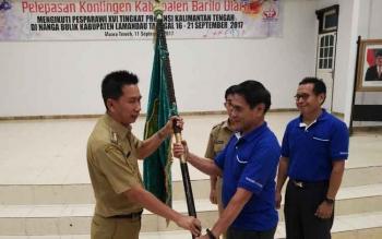 Bupati Nadalsyah menyerahkan bendera daerah kepada Ketua Kontingen Pesparawi Barito Utara Ompie Herby pada acara pelepasan, Senin (11/9/2017).