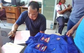 Ilham Pangestu saat diperiksa jaksa sambil diperlihatkan seragam polisi yang dicurinya.