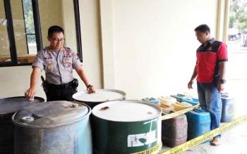 Kapolsek Pahandut AKP Roni Wijaya dan anggotanya menunjukan BBM tidak bertuan yang kini diamankan di sebuah parit, di kawasan Cemara Labat, Kelurahan Pahandut Seberang, Kota Palangka Raya, Rabu (13/9/2017).