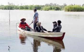 Bupati Seruyan Sudarsono dan isteri Ratna Mustika saat menaiki getek atau perahu kecil untuk melihat kondisi danau yang menjadi lokasi wisata di Desa Derangga.