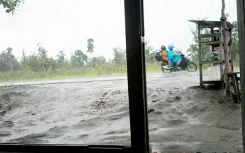 Pengendara sepeda motor melaju di Jalan Soekarno-Hatta Kasongan yang diguyur hujan, Minggu (17/9/2017).
