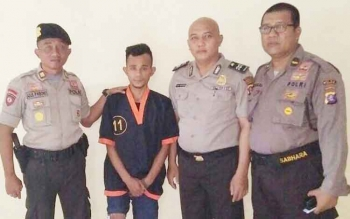 Tersangka pembunuh bidan cantik, ASP, saat berfoto bersama polisi.