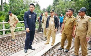 Bupati Barito Utara, H Nadalsyah didampingi tenaga teknis dinas PUPR saat melakukan pengecekan