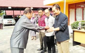 Ketua KPU Barito Utara, Aklamsyah menyerahkan hadiah kepada pemenang sayembara maskot dan jinggle Pilkada