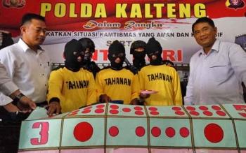 Direktur Reserse Kriminal Umum Polda Kalteng, Kombes Pol Ignatius Agung Prasetyoko (kanan), Wadirreskrimum, AKBP Alfian (kiri) menunjukan tersangka dan barang bukti judi gurak.