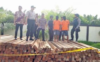 Kapolres Seruyan AKBP Nandang Mukmin saat menggiring dua tersangka beserta barang bukti berupa hasil olahan kayu ulin yang berhasil diamankan.