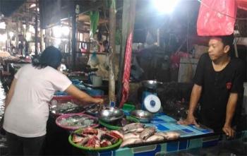 Seorang warga sedang membeli ikan di Pasar Kuala Kurun, Kabupaten Gunung Mas