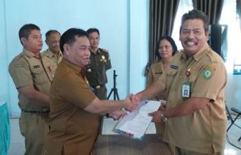 Pelaksana Tugas Sekda Kotim Halikinnor menyerahkan Surat Keputusan Mendagri kepada Kadisdukcapil yang baru Agus Suryo Wahyudi di acara serah terima jabatan, Senin (25/9/2017).