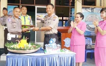 Kapolres Sukamara, AKBP Rade M Sinabela saat memberikan potongan kue kepada Kasat Lantas Polres Sukamara, Iptu Amzi Halim Permana.