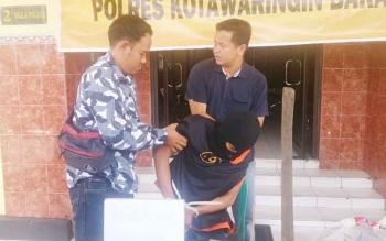 ASP harus dituntun dua anggota Reskrim Polres Kobar saat ekspos di Mapolres Kobar, akibat luka tembak di kakinya, Senin (25/9/2017)