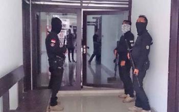 Anggota Polda Kalteng bersenjata lengkap mengawal empat ASN menuju ruang pidana umum (Pidum) Kejari Pangkalan Bun.