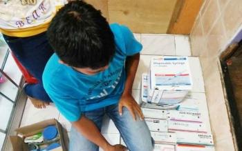 Tersangka Aspiani pemilik toko obat beserta barang bukti obat-obatan keras diamankan polisi karena tidak miliki izin edar farmasi.