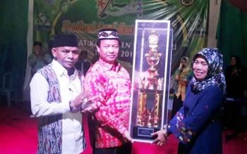Wakil Bupati Lamandau Sugiayarto didampingi Ketua DPD Lasqi Tommy Hermal Ibrahim menyerahkan piala bergilir kepada Camat Bulik, Atie Dieni, Selasa (26/9/2017) malam.