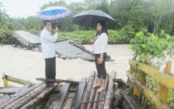 Anggota DPRD Gunung Mas, Lily Rusnikasi (kanan) mantau jembatan Sungai Rawi yang amruk diterjang air, Rabu (27/9/2017)