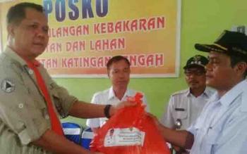 Kepala BNPD Provinsi Kalteng, Dariansyah menyerahkan bantuan Gubernur Kalteng kepada salah seorang kepada desa disaksikan Bupati Sakariyas di Tumbang Samba, Rabu (27/9/2017).