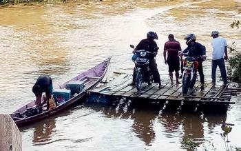 Masyarakat Kabupaten Gunung Mas terpaksa menggunakan rakit menyebrang Sungai Konjoi akibat jembatan hanyut tersapu air saat Sungai Konjoi meluap