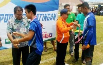 Ketua Panitia Porkab I Katingan, Nikodemus mengalungkan medali emas kepada pemain Kecamatan TSG yang menjadi juara cabang sepak bola, Jumat (29/9/2017).