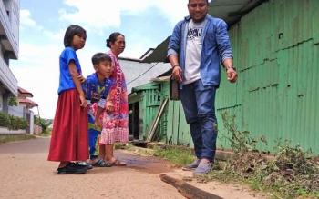 Sejumlah anak-anak dan warga saat melihat langsung ular puraca yang dibunuh di selokan, Senin (2/10/2017). .