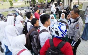 Anggota Satuan Lalu Lintas Polres Palangka Raya memberikan pemahaman kepada anak sekolah yang terjaring razia, Rabu (4/10/2017)