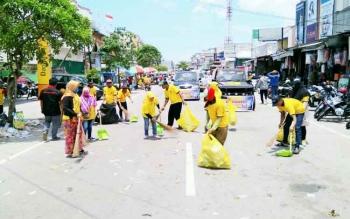 Kader DPD Partai Golkar Kabupaten Kobar membersihkan jalanan yang dilalui peserta Pawai Nasi Adab