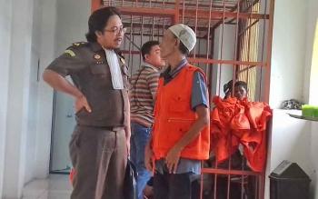 Asmansyah alias Hamsah terdakwa kasus zenith (pakai rompi) saat berbincang dengan jaksa.