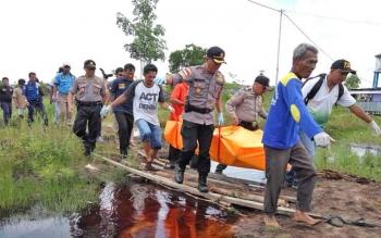 Aparat Polres Palangka Raya dan warga saat mengevakuasi jenazah Julkifi, Selasa (3/10/2017)