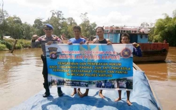 Bripka Triyanto dan para awak kapal KM Bulan Mas memegang spanduk tentang imbauan waspada terhadap paham radikalisme.