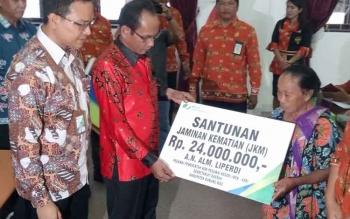 Bupati Gunung Mas Arton S Dohong didampingi Kepala BPJS Ketenagakerjaan Palangka Raya Ahmad Edi K menyerahkan santunan kepada ahli waris almarhum Liperdi secara simbolis, Kamis (5/10/2017).