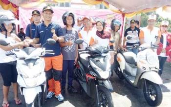 Bupati Gumas Arton S Dohong bersama isterinya Apristini AS Dohong (kanan) dan plh ketua KPU Provinsi Kalteng serta ketua KPU Gunung Mas menyerahkan hadian utama berupa sepeda motor kepada peserta jalan sehat yang beruntung, Jumat (6/10/2017).