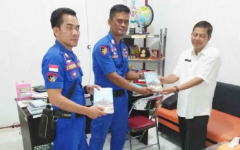 Kepala Dinas Perpustakaan Dan Kearsiapan Daerah Sukamara saat menyerahkan buku kepada Kamarnit Pol Airud Kuala Jelai Brigadir Yadi Supiandi.