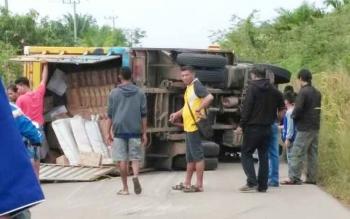 Sejumlah warga ikut mengevakuasi truk bok yang terbalik di Parenggean, Kotim, Senin (9/10/2017)