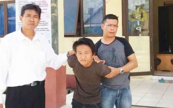Pelaku sedang diapit polisi saat diamankan di Polsek Dusun Selatan