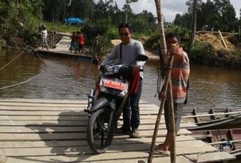 Anggota DPRD Kabupaten Gunung Mas Herbert Y Asin saat menyeberangi Sungai Konjoi menggunakan rakit, Selasa (10/10/2017).