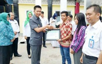 Bupati Barito Utara Nadalsyah saat menyerahkan kartu JKN secara simbolis kepada aparatur Desa Kandui, Kamis (12/10/2017).