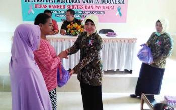 Ketua IAD Pulang Pisau menyerahkan sembako kepada peserta gerakan nasional deteksi dini wanita Indonesia bebas kanker serviks dan payudara.