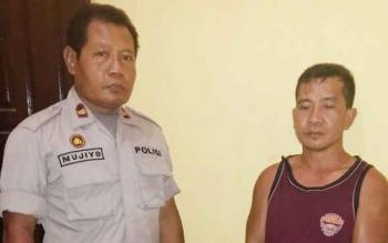 Kapolsek Aruta Iptu Mujiyo (kiri) menunjukan tersangka Edi yang diduga mempekosa anak tirinya pada Kamis (12/10/2017).