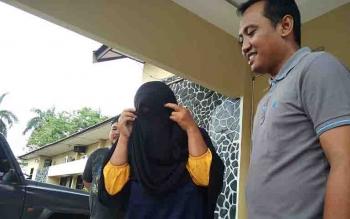 Tersangka bandar togel berusaha menutupi wajahnya saat diekspos di Polres Kotim.