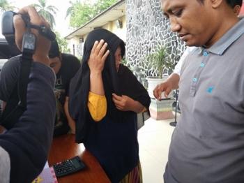 SH, tersangka penjual togel, menutup wajahnya dengan kerudung saat disorot kamera wartawan, Sabtu (14/10/2017).\\r\\n