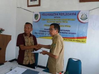 Kepala Disdagrin Barito Utara Hajrannoor menyerahkan dokumen kesepahaman tentang pembayaran retribusi pasar kepada Kepala Kejaksaan Negeri Barito Utara Basrulnas, Senin (9/10/2017).